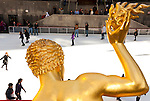 FEBRUARY 27, 2011 - MANHATTAN - Gold statue of Prometheus closeup from behind with skaters at Rockefeller Center Staking Rink midday on February 27, 2011 in New York City, NY, USA. Sharp focus on statue of the god bringing fire to man. (Editorial Use Only)