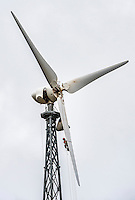 Man repairing the propeller of a wind turbine.