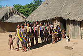 Pará State, Brazil. Aldeia Pukararankre (Kayapo). Women coming out of a house to dance.