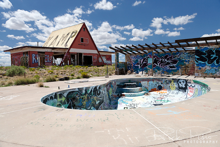 "Pool and camp store at Two Guns in Arizona. Two Guns is located in Arizona, east of Flagstaff, on what was formerly Route 66. Two Guns was originally called ""Canyon Lodge"" when the National Trail Highway moved westward. Later, the National Trail was re-named Route 66, the site's name was changed to Two Guns, because the proprietor of the facilities located there was one Henry E. Miller, who called himself ""Two Gun Miller."" During the heyday of Route 66, Two Guns became one of the numerous tourist traps along the way, with a gas station, overnighting accommodations, a food emporium, as well as a zoo. Two Guns went into decline with the building of the Interstate."