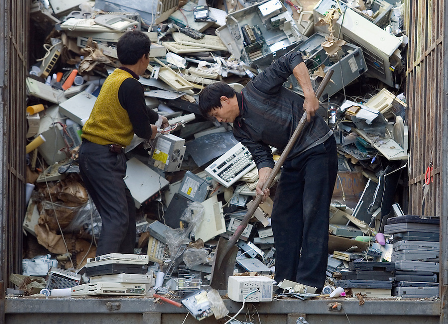 Chinese workers receive a truckload of electronic trash including old laptops, keyboards, terminals, and desk top computers in Guiyu, China.