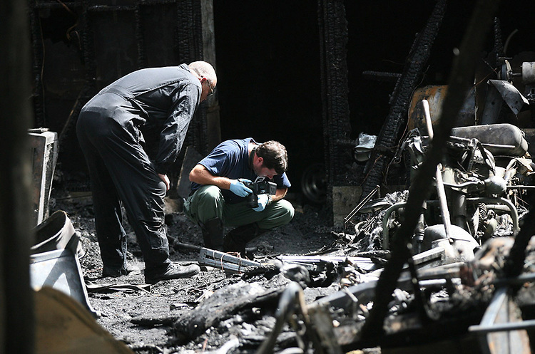 SBI agent Reid Sasser records some burned material as Craven County Ast. Fire Marshall Ira Whitford assists Wednesday morning investigating the cause of a fire at 335 Sanders Lane. The fire consumed a detached garage with four vehicles and a motorcycle.