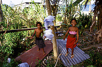 Two smiling girls play with home made tether ball in their front yard, Yap, Micronesia.