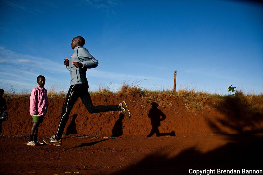 Young children watch as Johanna Kariankei, 17, runs in the early morning close to the Kenyan town of Iten. Athletes there are being hit by the economic crisis which is robbing races and runners of crucial sponsorship. Johanna, who has never run outside Kenya, hopes the crisis will pass and he will be able to fulfil his dream of winning good money from international races.