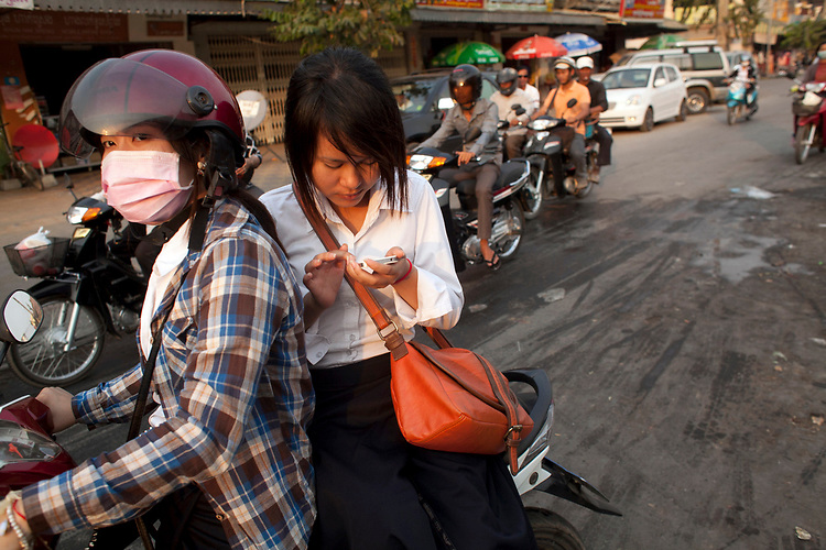 A young woman text from the back of a motorbike in Phnom Penh, Cambodia. <br /> <br /> Photos &copy; Dennis Drenner 2013.