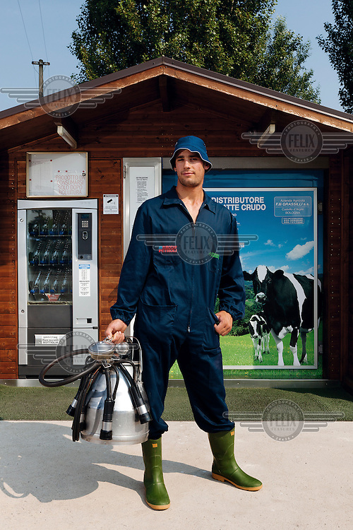 A dairy farmer stands in front of the fresh milk dispenser that he has had installed.