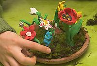Kinder basteln Frühjahrsblumen aus Knete, Bastelei, Verschiedene Blumen (Hyazinthe, Tulpe, Narzisse, Osterglocke u.a.) auf Tonteller, wird zusätzlich mit Moos dekoriert