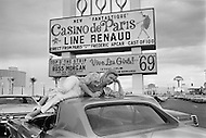 March 1969, Las Vegas, Nevada, USA. French singer and actress Line Renaud lying on a car under a billboard at the Dunes Casino in Las Vegas in 1969. Renaud was one of France's most-loved, respected, and successful entertainers.