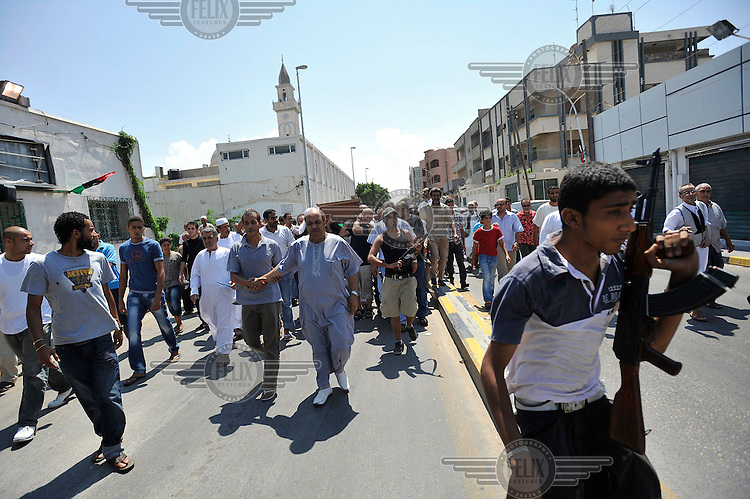 A funeral procession of a deaf rebel fighter on a street in Tripoli. After a six month revolution, rebel forces finally managed to break into Tripoli and have taken control of Bab al-Aziziyah, Col Gaddafi's compound and residence. Few remain that are loyal to Gaddafi in the city; it is seeming that the 42 year regime has come to an end. Gaddafi is currently on the run.