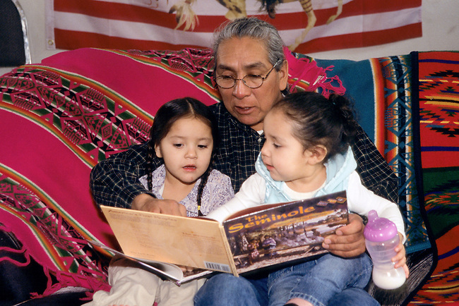 Native American family of Shoshone Bannock grandfather reading a story book to his two young grand-daughters