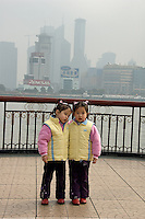 Twin sister on the bund, in front of Pudong skyscraper, posing to their father..Shanghai, February 2006.