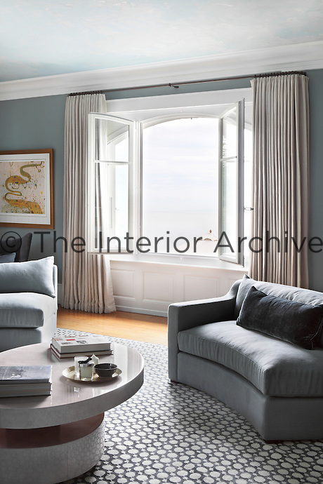 Elegantly pleated curtains frame a view across the lake from the upstairs living room