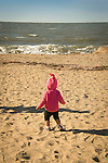 Toddler girl child on beach looking at ocean.