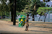 Rio de Janeiro, Brazil. Barefoot boy carrying plastic Brazilian flags which he is selling to football supporters