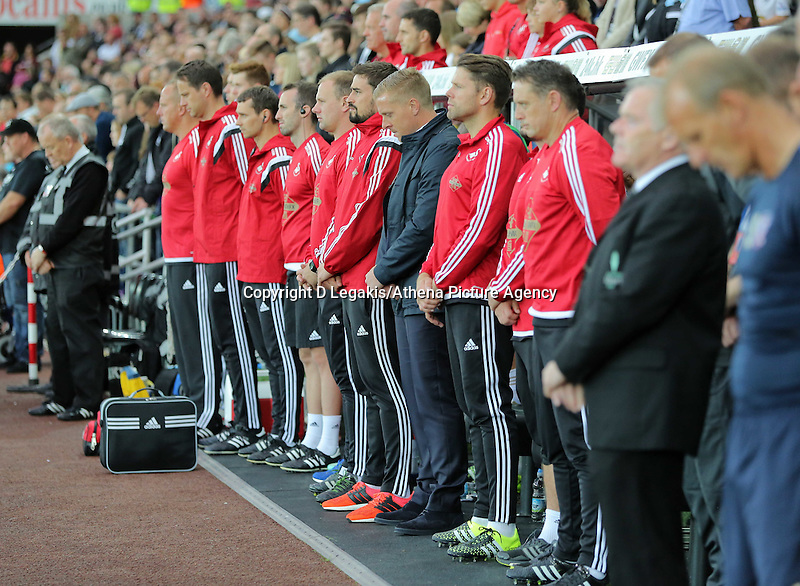 Pictured: Swansea manager Garry Monk (C) observes a minute's silence with his colleagues before kick off Tuesday 25 August 2015<br /> Re: Capital One Cup, Round Two, Swansea City v York City at the Liberty Stadium, Swansea, UK.