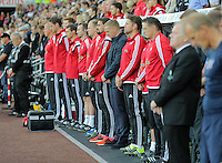 Pictured: Swansea manager Garry Monk (C) observes a minute's silence with his colleagues before kick off Tuesday 25 August 2015<br />