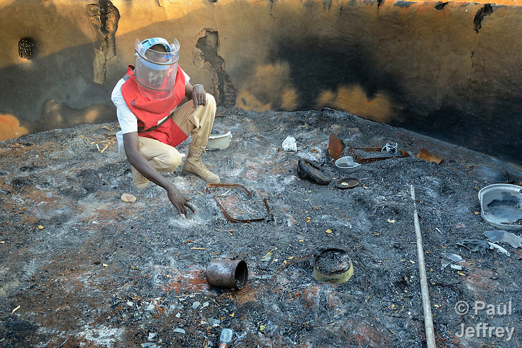 A member of an ACT Alliance team searches for unexploded ordnance in the charred remains of a house near the South Sudan town of Bor, which has been the scene of heavy fighting between government troops and rebels since a dispute within the ruling party turned violent in December 2013 and quickly ripped the newly independent nation along ethnic and tribal lines. The explosive ordnance disposal team is part of the humanitarian mine action program of Dan Church Aid, a member of the ACT Alliance. The program also deploys mine risk education teams to help villagers identify and understand the dangers of unexploded ordnance and land mines from this most recent conflict as well as ordnance left over from decades of civil war.