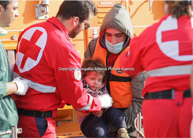 Pictured: A young child is helped by Red Cross personnel  Thursday 27 November 2014<br /> Re: One of the largest refugee boats in recent months has disembarked refugees in Ierapetra, Crete. The freighter Baris, carrying 700 people thought to be from Syria and Afghanistan, is being towed by a Greek frigate.<br /> Officials and Red Cross volunteers prepared an indoor basketball stadium as interim shelter in the southern Cretan port town of Ierapetra on Wednesday ahead of the migrants' expected arrival.<br /> Greek officials said the Baris, which lost propulsion on Tuesday, was being towed slowly in poor sea conditions and would arrive after nightfall, probably early Thursday.<br /> They said it was unclear which Mediterranean location had been the departure point for the 77-meter (254-foot) vessel, which was sailing under the flag of the Pacific nation of Kiribati.