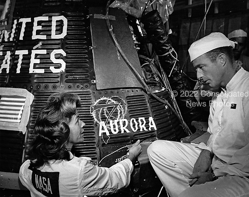 Cecelia Bibby, an employee of the Chrysler Corporation, left, paints the name &quot;Aurora 7&quot; on a Project Mercury spacecraft for the United States' second manned orbital flight while mission pilot M. Scott Carpenter, right, looks on, at Cape Canaveral, Florida on May 19, 1962.<br /> Credit: NASA via CNP