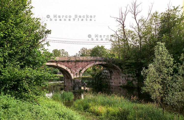 Nosate (Milano), Parco della Valle del Ticino. Il vecchio tratto iniziale del Naviglio Grande, non più attivo. Un pescatore a un vecchio ponte --- Nosate (Milan), Natural Park of Ticino valley. The old initial stretch of the canal Naviglio Grande, no longer active. A fisherman by an old bridge