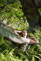Woman lying in hammock above ferns
