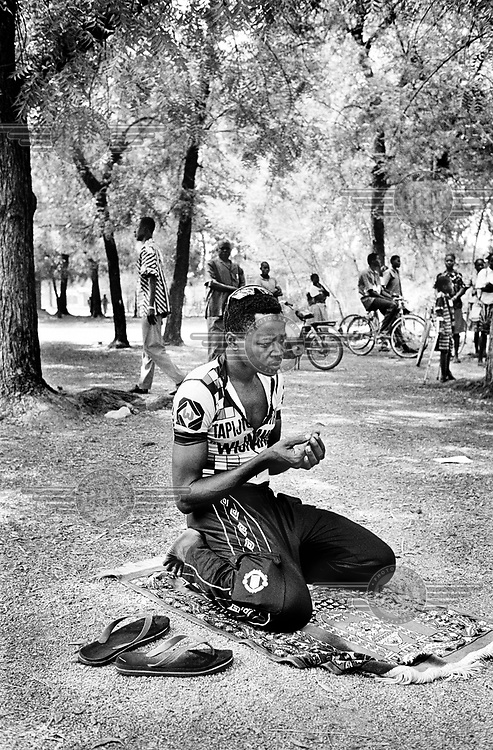 ©Chris Keulen/Panos Pictures..Burkina Faso, Sabou, 17/11/2000.Musliman and cyclist Abdoul Salam Zakari from Niger praying before the start of the 3th day in the Tour du Faso just beside the road.