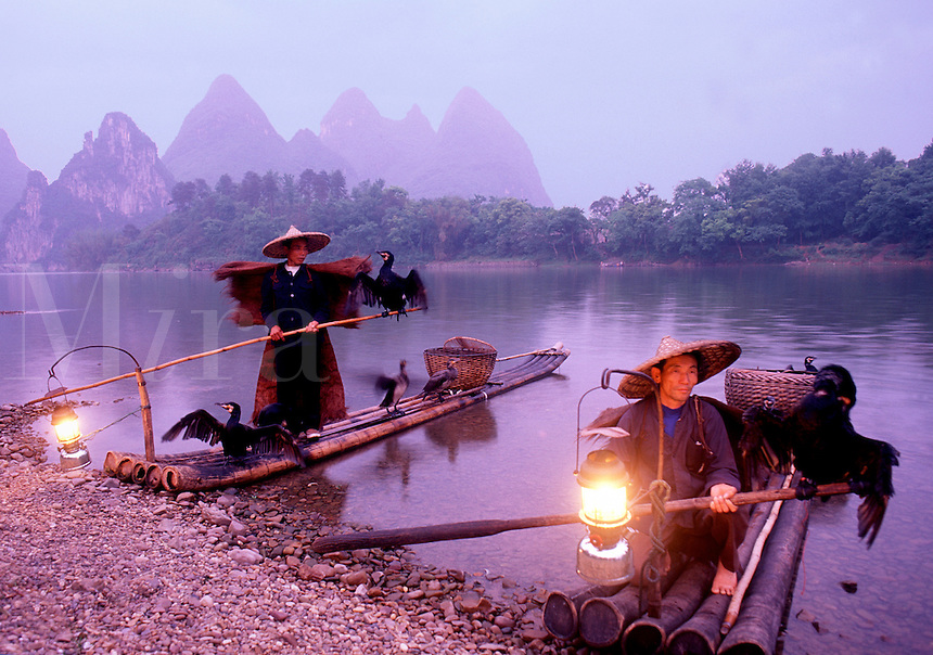 Fishermen in traditional attire with Cormorant fishing birds, lanterns and bamboo rafts on the Li River at dusk. Yangshou, China.