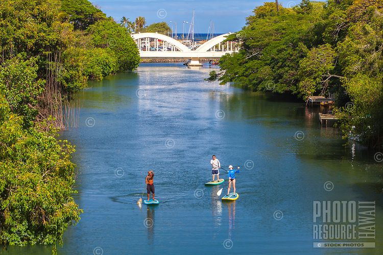 Standup paddleboarders on Anahulu Stream in Haleiwa, North Shore, O'ahu.