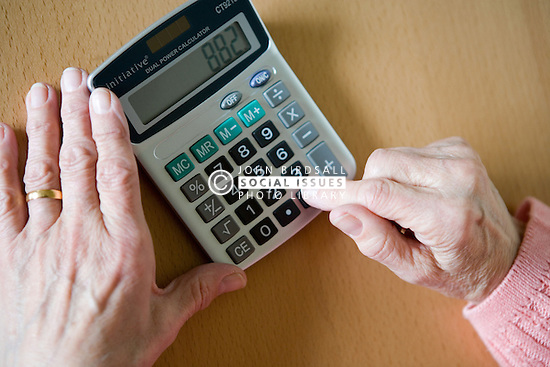 Older woman doing a calculation on a calculator,