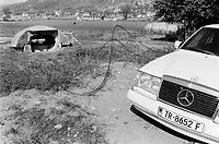 Albania. Province of Tirana. Village of Vagarr. An old derelict bunker and a new expensive mercedes car. Enver Hoxha (1908-1985) was for 40 years a dictator and a communist leader. He decided after the historic break with Russia in 1961 to protect his country from any invaders by investing in a massive fortification (more than a million bunkers were built over the years till 1985). © 2003 Didier Ruef