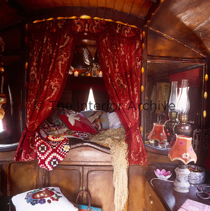 Inside a Romany caravan with a bed area piled with cushions and screened by red curtains. Vibrant colours and patterns are used to create a intimate, cosy atmosphere.