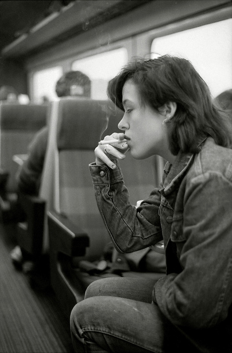 A girl smoking a cigarette on a train in England.December 1983.
