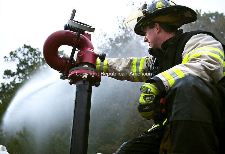 Wolcott, CT- 03 October 2015-100315CM06- ​ Wolcott volunteer firefighter ​Bruce Cyr mans a deck water gun at the Wolcott Elementary School on Saturday.  Departments from Wolcott, Bristol, Southington and Prospect participated in the training exercise.     Christopher Massa Republican-American