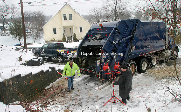 WOLCOTT CT.-24 FEBUARY 2009-022410DA03-  Investigators look over the scene where Eric Hassan, 24 of Waterbury was killed in Wolcott Wednesday morning when a garbage truck backed into him.<br /> Republican-American  Darlene Douty