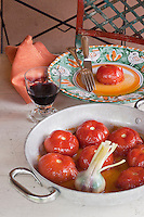 Roasted whole tomatoes with garlic served in a white enamelled pot and accompanied with a glass of local red wine