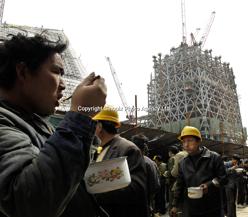Chinese workers have lunch at the construction site of the new headquarters for China Central Television (CCTV) in Beijing, China. China's CCTV and other important organisations and businesses are gobbling up space in the CBD. The area is to become a new kind of hub for business Beijing following completion..