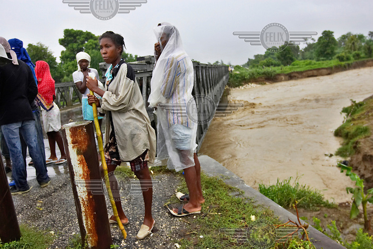 People stand beside a river during Hurricane Gustav.