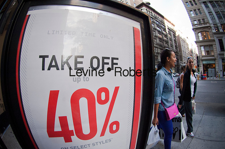 A clothing store seen in the Chelsea neighborhood in New York advertises its sales on Sunday, September 16, 2012.  (© Frances M. Roberts)