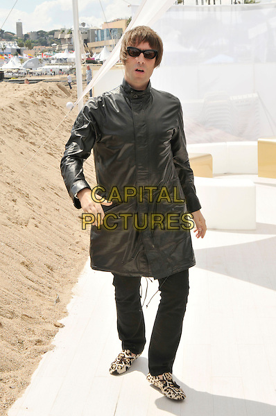 "LIAM GALLAGHER.his newest production company 'In 1 Productions' announces thay will produce a Beatles film based on the book by Richard DiLello:.""The Longest Cocktail Party' photocall.63rd International Cannes Film Festival, France.14th May 2010.full length black leather jacket jeans denim sunglasses shades leopard print loafers shoes mouth open.CAP/PL.©Phil Loftus/Capital Pictures."