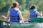 Two young multi ethnic adult women in a canoe paddle on the Fox River in Yorkville Illinois USA