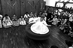 """Mae Shirley de Xango dance in circles to invoke spirits during a spiritual session, in her temple in Montevideo, Uruguay. Umbanda followers believe a spiritual leader can act as a medium in which the spirits can """"incorporate"""" to his/her body. Photo by Quique Kierszenbaum"""