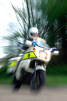 Zoom in on a police motor clyclist