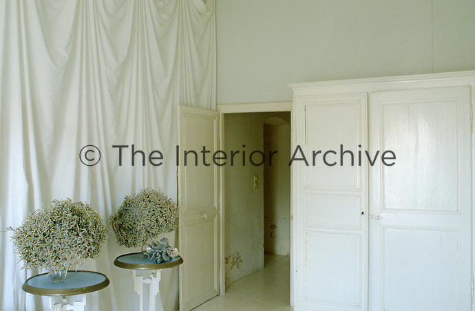 Resembling two 18th century powdered wigs a pair of vases containing dried flower arrangements stand on matching cafe tables in front of a white curtain in the entrance hall