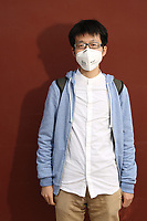 "Wu (24), a student, stands next to the red walls of the Lama Temple in Beijing. ""When I left home today, I was coughing a lot, so I put it [the mask] on. Before. I only wore it when there was heavy pollution. Now, I wear it everyday."" PM2.5 reading - 200 - Unhealthy"