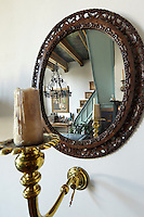 The staircase leading to the top floor of the house  reflected in an 18th Dutch woodcarved oval mirror
