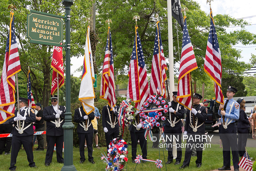 Merrick, New York, U.S. - May 26, 2014 - Members of the North Merrick Fire Dept. hold flags at The Merrick Memorial Day Parade and Ceremony, hosted by American Legion Post 1282 of Merrick, honoring those who died in war while serving in the United States military.