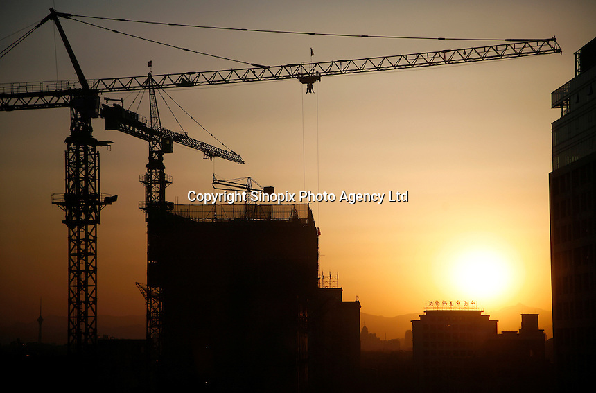 Silhouettes of construction cranes at a building site for new apartments in Beijing, China..03 Apr 2007