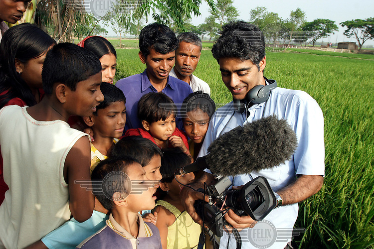 Journalist Ashok Prasad shows film footage to the villagers of Dinajpur.