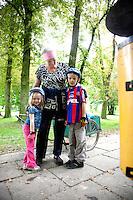 Friendly Polish woman park attendant posing with children bicyclers wearing helmets. Paderewski Park Rzeczyca Central Poland