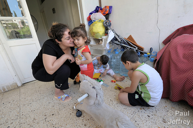 Farah Faris, who is 20 months old, gets a kiss from her mother, Rana Ramzi, in their small apartment in Beirut. Ramzi's husband was killed February 29, 2008, in Mosul, Iraq, while working as a driver and assistant to the Chaldean archbishop of Mosul, Archbishop Faraj Rahho, who was later found dead. Ramzi and her three children (including Stephen, right, and Milad) fled Iraq in May and live as refugees in Lebanon. They have received assistance from the Caritas Lebanon Migrant Center, which is funded by Catholic Relief Services, the relief and development agency of the U.S. Catholic community.
